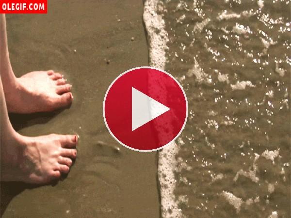 Mujer remojándose los pies en la orilla del mar