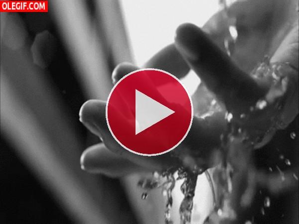 Agua fluyendo sobre la palma de una mano