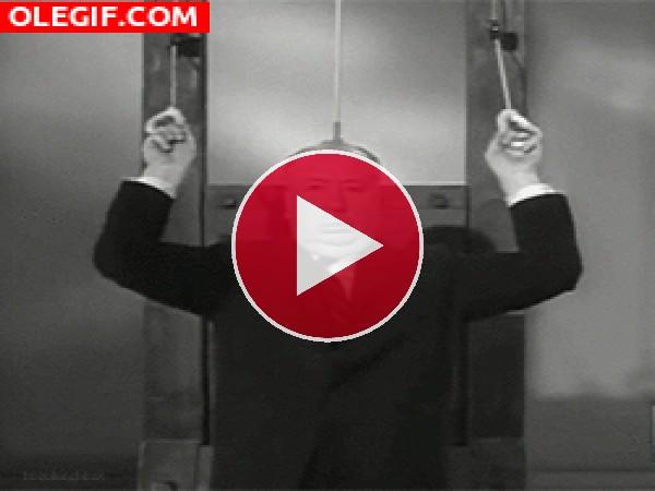 GIF: Alfred Hitchcock haciendo bíceps con una guillotina