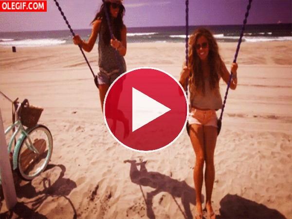 Amigas columpiándose en la playa
