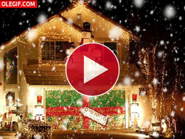 Nieva sobre una casa iluminada por Navidad