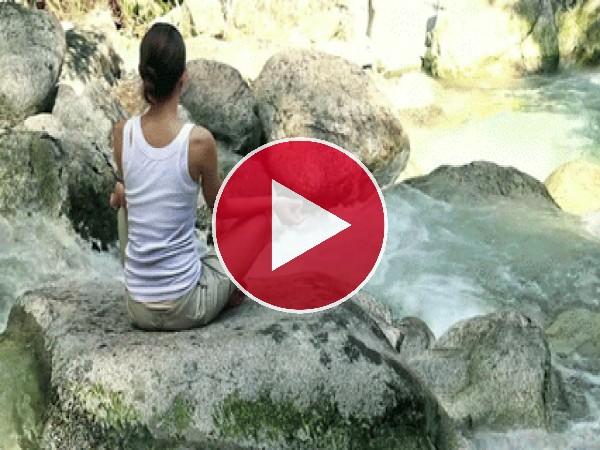 Meditando sobre una roca del río