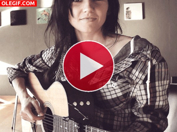 Una chica guapa tocando la guitarra