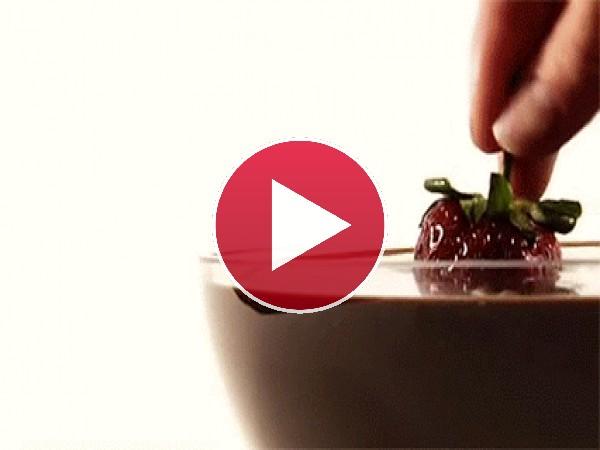Mojando una fresa en chocolate fundido