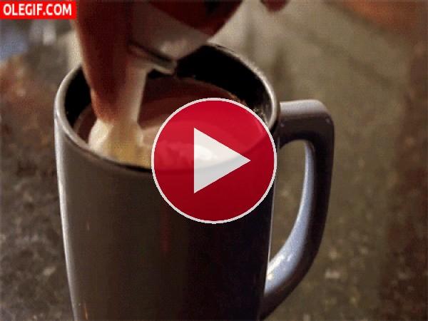 Poniendo nata montada sobre un chocolate caliente