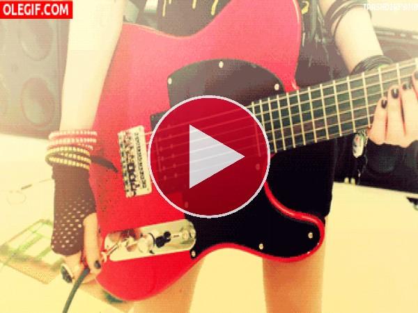 Chica conectando la guitarra eléctrica